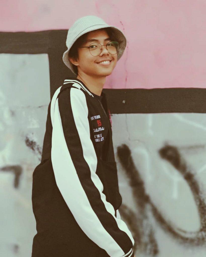Senyum Fahmi Nasrullah Menggunakan Topi dan Kacamata